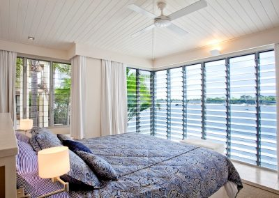 A wall of Altair Louvres and a ceilling fan keep this bedroom cool and comfortable in this hot climate.