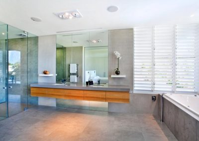 This bathroom uses Altair Louvre Windows with white aluminium blades for privacy and ventilation.